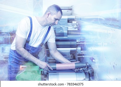 Printer operator next to the printing machine, holding printing cylinder with polymer relief plate stuck on it. Scene showing the preparation for the printing process. Stack press proces