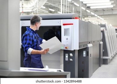 Printer in the printing house. Operation of the printing machine.