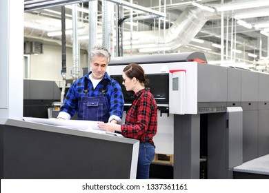 Printing house. The printer and the customer at the stage are watching the printout.