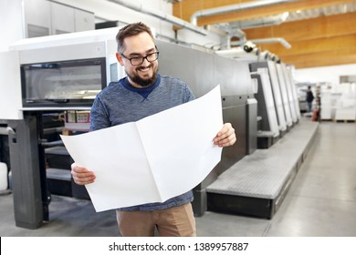 Printing house. Satisfied man is watching the printout.