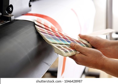 Printing machine, color print. The printer checks the color of the printout on the color sampler.