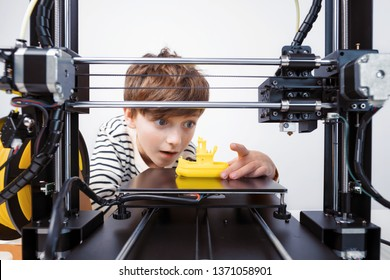 Printing on 3D printer figurines of toys from white plastic close-up. The boy happily and emotionally takes the finished printed figure from the working platform of the printer and goes into the play
