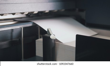 Printing press machine takes sheet of paper in action in the printing production line