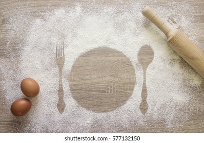 Prints of dish, fork and spoon in the flour with uncooked eggs and rolling pin. The concept of a recipe or cooking.  Space for text.