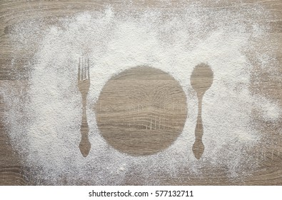 Prints of dish, fork and spoon in the flour. White flour on the wooden table. Space for text.