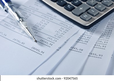 Prints of financial report on sheets with pen and calculator