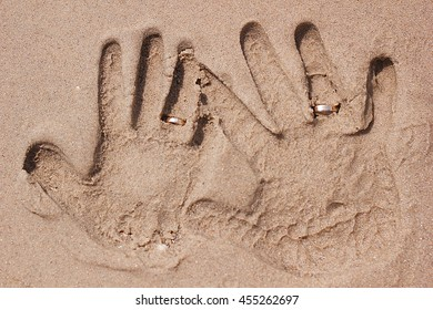Prints of male and female hand in the sand with wedding rings . Honeymoon on the sea coast .