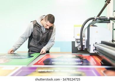 Druckfachtechniker arbeitet an einer großen CNC-Maschine für numerische Steuerungs- und Schneidmaschine