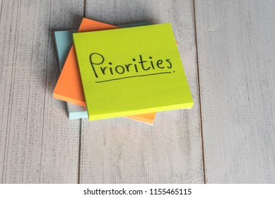Priorities reminder handwriting on sticky note on white background, top view.