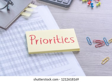 Priorities reminder handwriting on sticky note and document on wooden background, Business concept, top view
