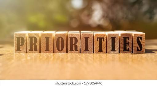 PRIORITIES word made with wood building blocks.