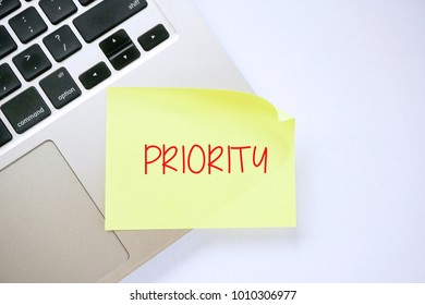 PRIORITY on sticky note pasted on keyboard. Top view design