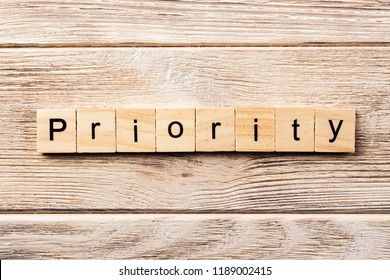 priority word written on wood block. priority text on table, concept.