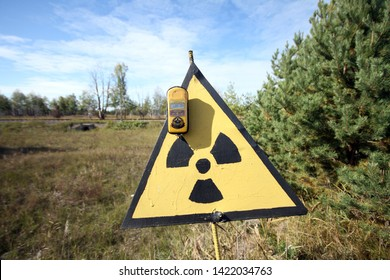 Pripyat, Chernobyl/ Ukraine - October, 5th, 2018: Radiation meter in front of a sign with the radiation symbol in the Chernobyl region.