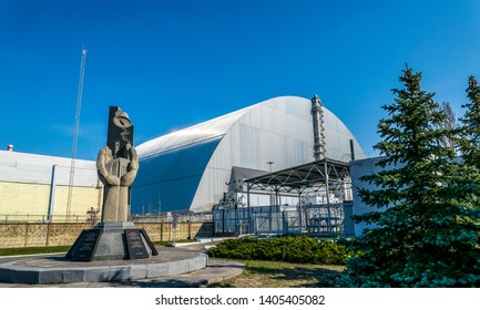 Pripyat city Kiev region / Ukraine - April 13 2019: metal hangar shelter on the emergency fourth power unit of the Chernobyl nuclear power plant and a memorial to the victims of the Chernobyl disaste