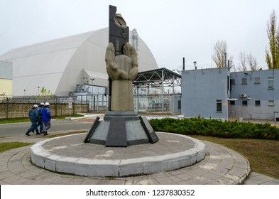 "PRIPYAT, UKRAINE - NOVEMBER 11, 2018: Monument to liquidators of accident at Chernobyl NPP on background of object ""Shelter"" over 4th power unit in Exclusion Zone. Unknown employees go to NPP"