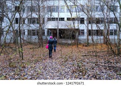 PRIPYAT, UKRAINE - NOVEMBER 11, 2018: Unknown tourists go to abandoned school building in dead ghost town of Pripyat in Chernobyl NPP alienation zone, Ukraine