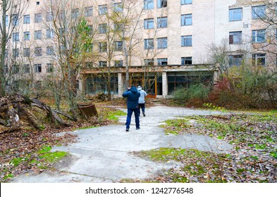 PRIPYAT, UKRAINE - NOVEMBER 11, 2018: Unknown tourists go to abandoned building of hospital No. 126 in dead ghost town of Pripyat in Chernobyl NPP alienation zone, Ukraine