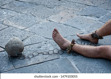 Prisioner with ball and chain in the court of the prison. Close up. Concept of inhuman and degrading detention conditions.
