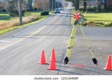 A prism attached on a tripod is being used as a target for measuring distance by professional surveyors collecting date for road work.