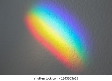 A prism casts a rainbow of light on a textured surface