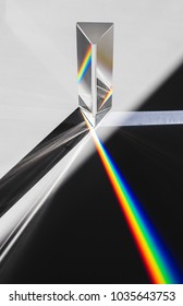 A prism dispersing sunlight splitting into a spectrum on a white background.