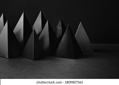 Prism pyramid objects on black gray background. Abstract geometrical figures still life composition