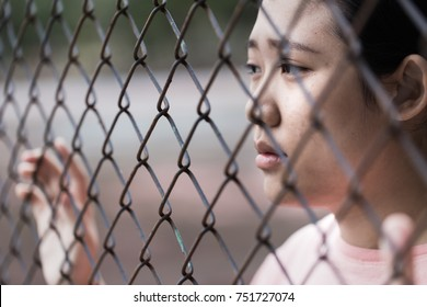 prison asian teen behide cage with sad in jail