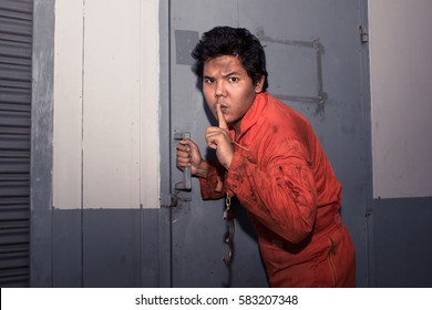 Prison Breaker in orange jump suit making silence gesture while trying to open metal door, Shhh!!