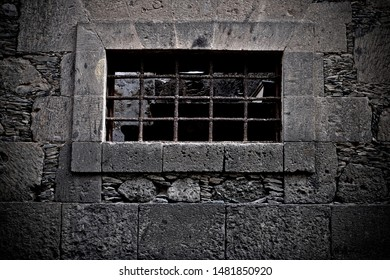 A prison cell, a barred window.