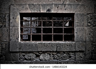 Prison cell window with bars, old stone citadel architecture detail.