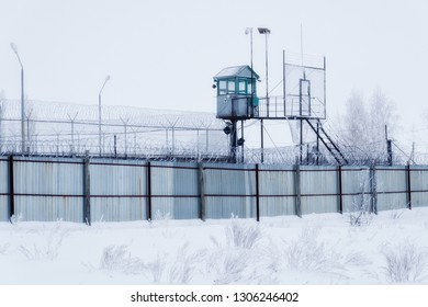 Prison guarding tower, fence with barbed wire.