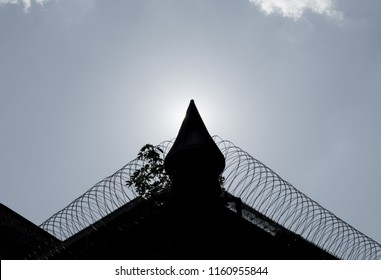 A prison wall with a tower and barbed wire