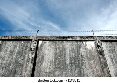 the prison walls with high walls and barbed iron wire
