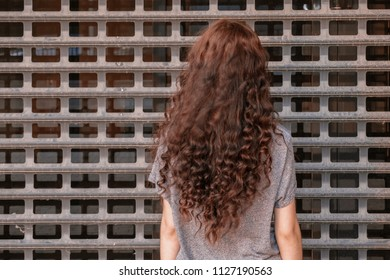 Prisoner girl looking at metal fence of jail, image with copyspace