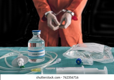 Prisoner handcuffed to death by lethal injection, vial with sodium thiopental and syringe on top of a table, conceptual image