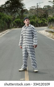 A prisoner in jail clothes walking down a street.