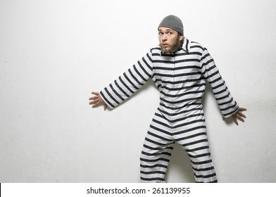 A prisoner in a jailhouse jumpsuit making crazy faces