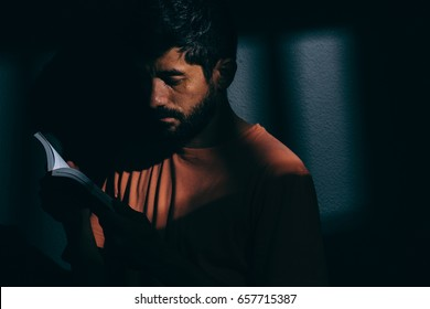 Prisoner man in dark cell reading a book or bible