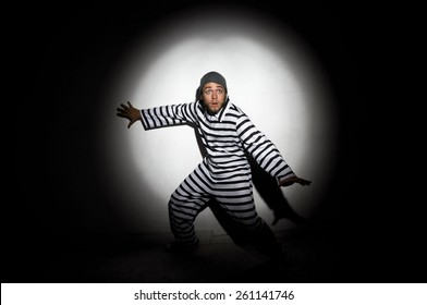 A prisoner trying to escape from prison being caught by a search light