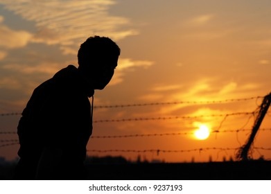 A prisoner yearning for freedom at sunset