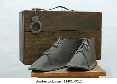 A prisoner's set: boots, suitcase and handcuffs on the nightstand.