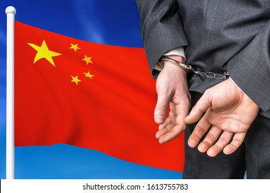 Prisons and corruption in China. Businessman with handcuffs on national flag background.