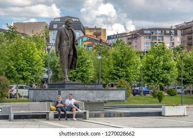 Pristina, Kosovo - June 2nd 2018 - Locals sitting in a public open air in downtown Pristina, the capital of Kosovo with trees in the background