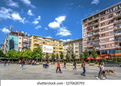 Pristina, Kosovo - May 30th 2018 - Big group of people walking in front of colorful buildings in a blue sky day in Kosovo