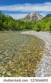 The pristine alpine water of Azusa River flowing in front of landscape view of Mount Hotaka-Dake on a sunny, blue sky day in Japanese Alps village of Kamikochi, Nagano, Japan.