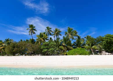 pristine empty island at fiji, south pacific, with blue sky, palm trees, white sand beach and turquoise lagoon