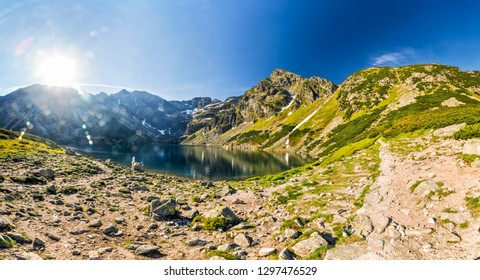 Pristine mountain lake surrounded by mountain peaks of High Tatras in Slovakia on sunny summer day.