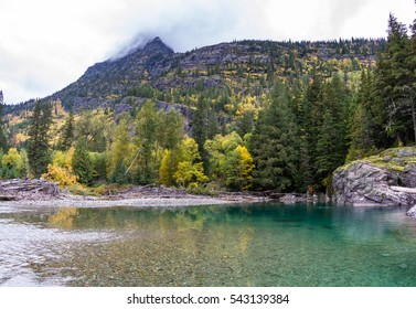 pristine river flowing from melting glaciers and snow melt in the mountains of Glacier NP inMontana with color changing autumn vegetation in the baks and mountains