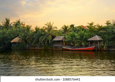 Pristine riverbank at sunset, palms trees, a red boat and bungalows, situated at the Praek Tuek Chhu River in Kampot Province in southern Cambodia, Asia. Natural asian riverside landscape